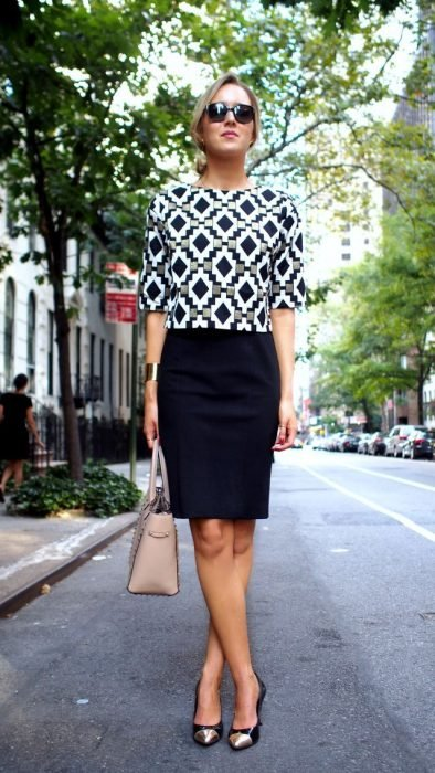 Office outfits. Girl wearing a black skirt and a blouse with tribal print