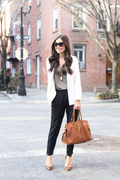 Office outfit. Girl wearing a black pants, a brown blouse and an ivory jacket