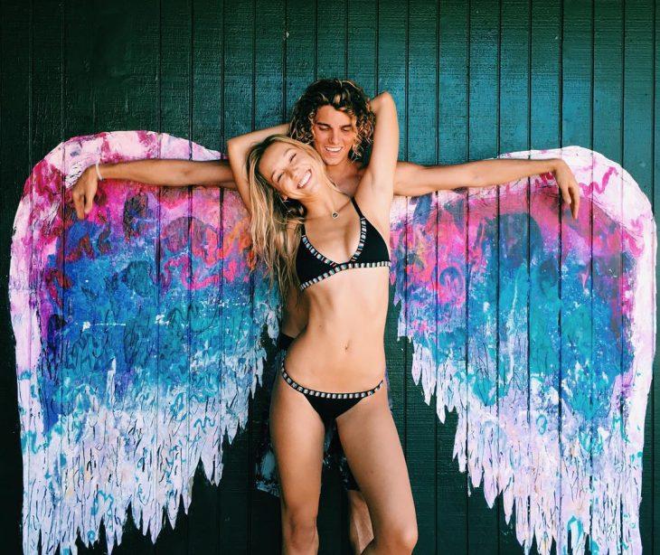 Jay Alvarrez y Alexis Ren Pareja de novios que viajan al rededor del mundo sobre unas alas pintadas en una pared