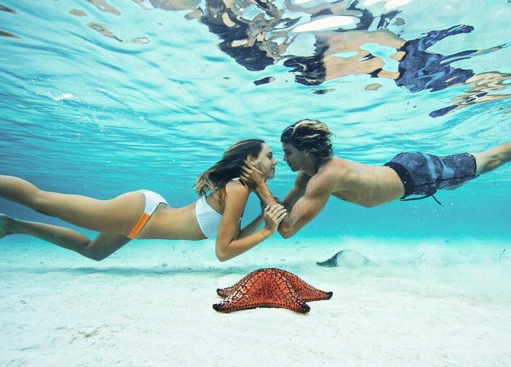 Jay Alvarrez y Alexis Ren Pareja de novios que viajan al rededor del mundo besándose bajo el mar
