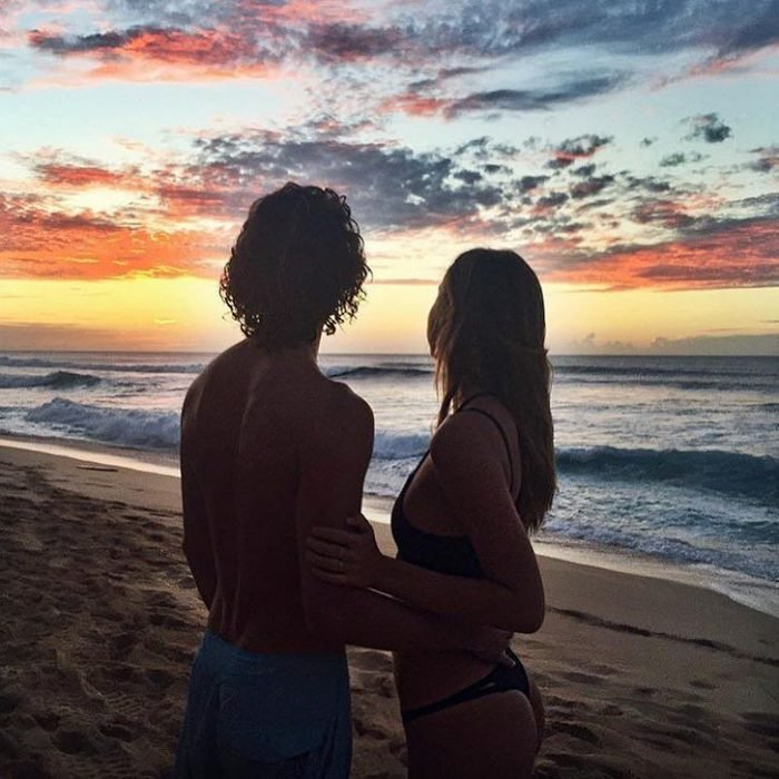 Jay Alvarrez y Alexis Ren Pareja de novios que viajan al rededor del mundo viendo una puesta de sol