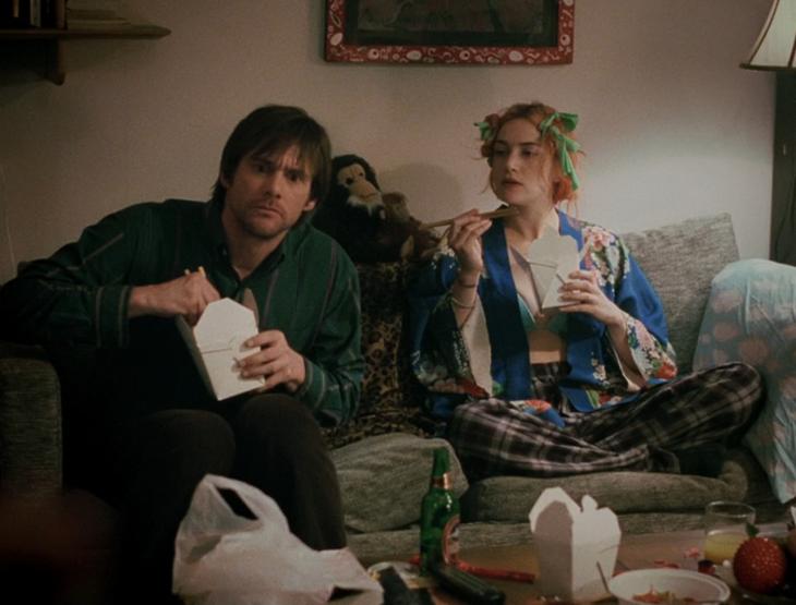 Escena de la película eterno resplandor de una mente sin recuerdos. Pareja sentada en el sofá comiendo