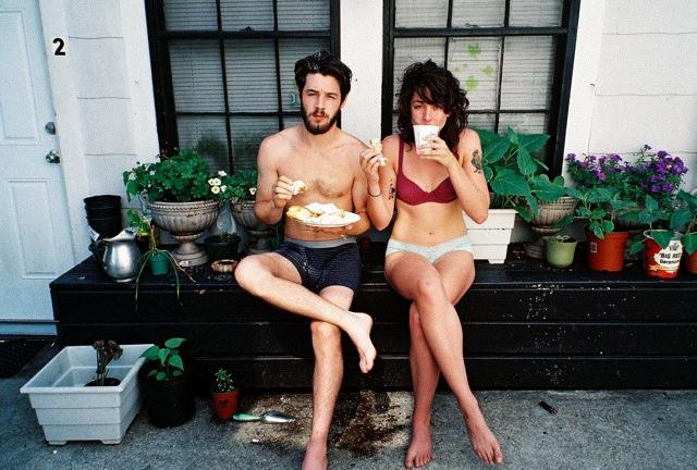Pareja de novios comiendo mientras están sentados fuera de su casa