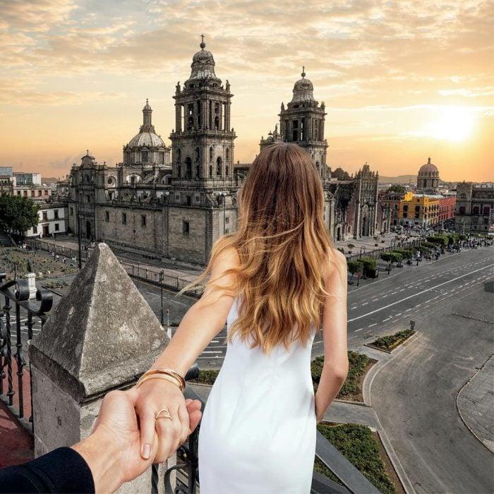 Chica dandole la espalda a un chico mientras le sujeta una mano y ven una catedral