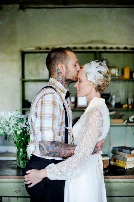 Chico besando a una chica en la frente mientras está vestida de novia