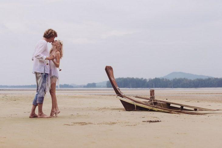 Pareja de novios parados sobre la arena del mar besándose
