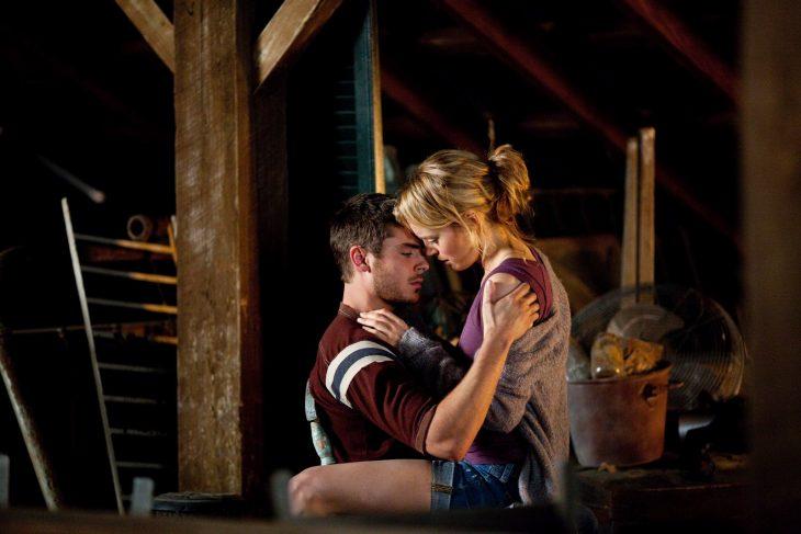 Chico y chica sentados en una silla frente a frente besándose