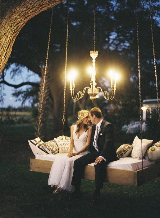 Pareja de novios recién casados sentados sobre una hamaca