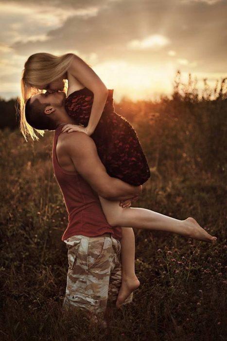 Chico abrazando a una chica mientras la besa en medio de un campo
