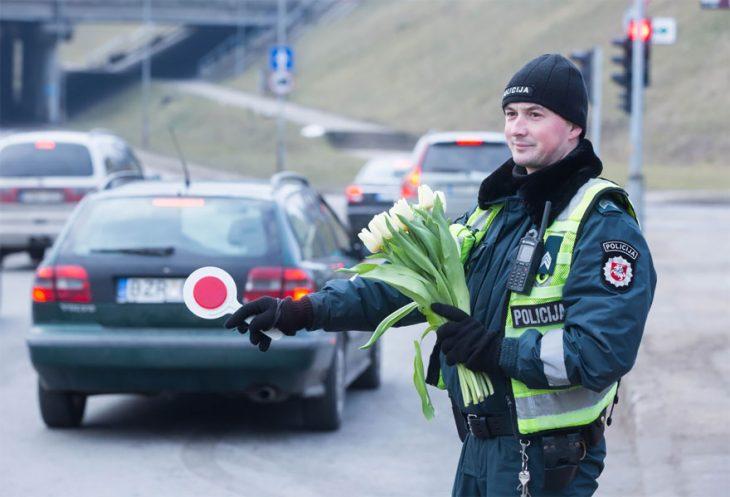 Policía sujetando un ramo de tulipanes en medio de la acera