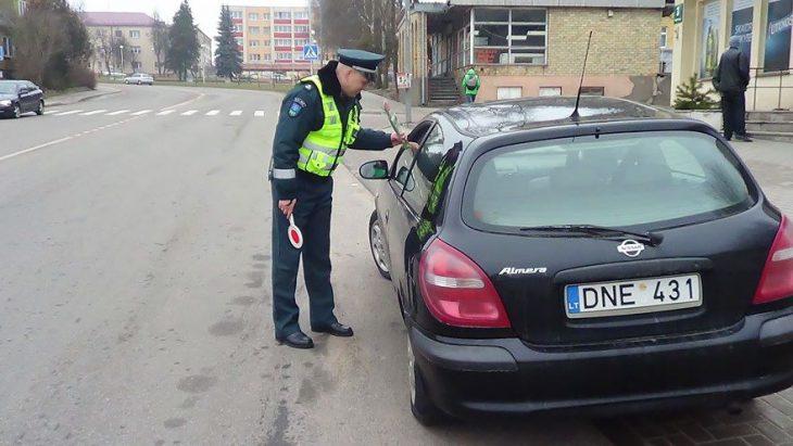 Policia entregando flores a una mujer que está conduciendo
