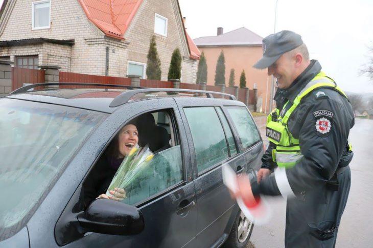 Policía entregando flores a una mujer que está conduciendo
