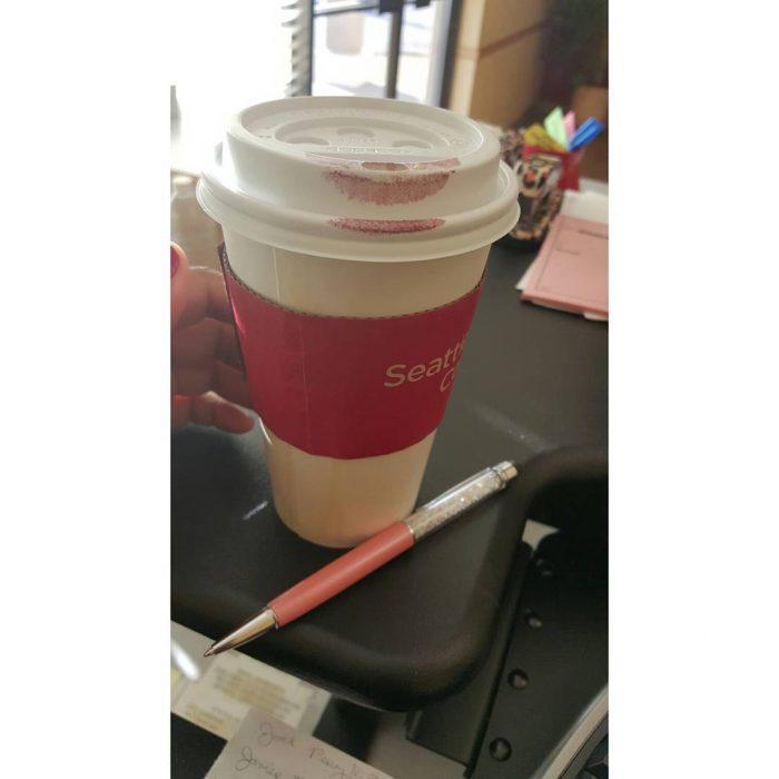 Vaso de café lleno de lápiz labial de color rojo