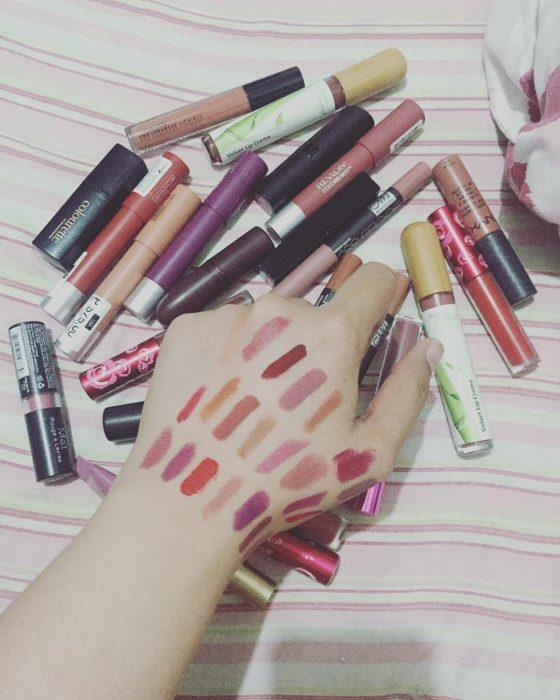 Mano de una chica llena de colores de lápiz labial