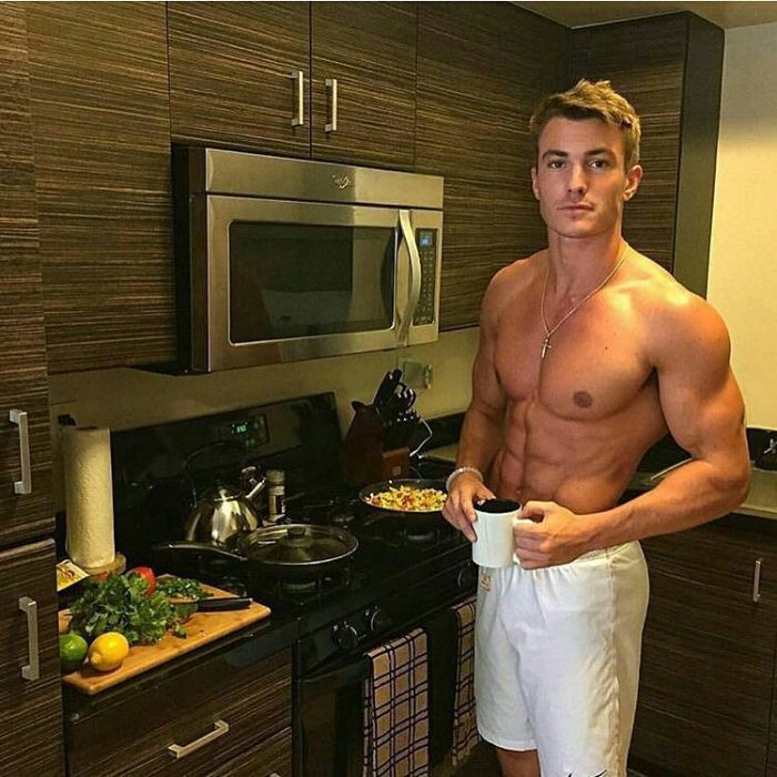 Chico guapo con una taza de café en la cocina