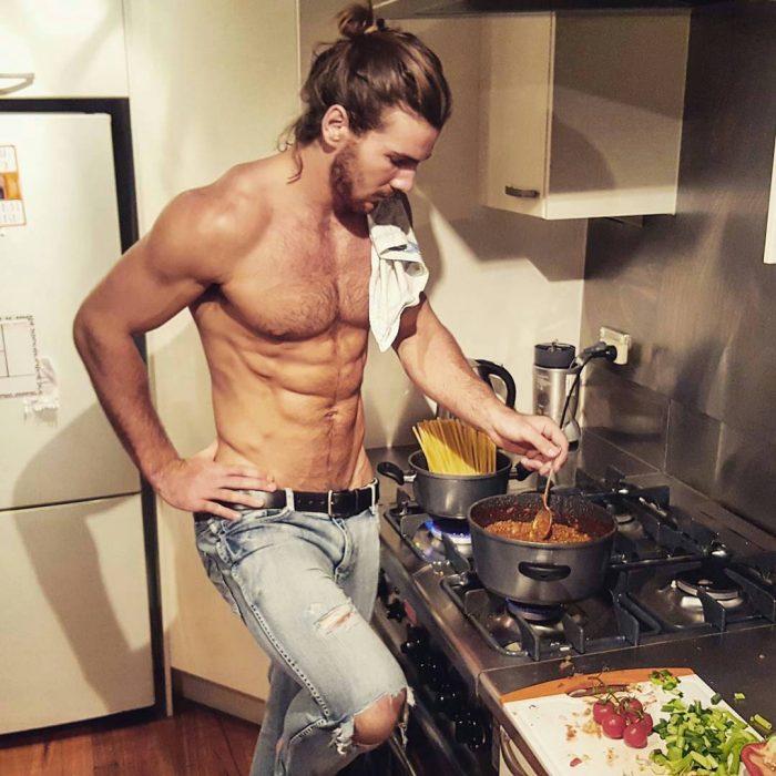 Chico guapo preparando comida en la estufa