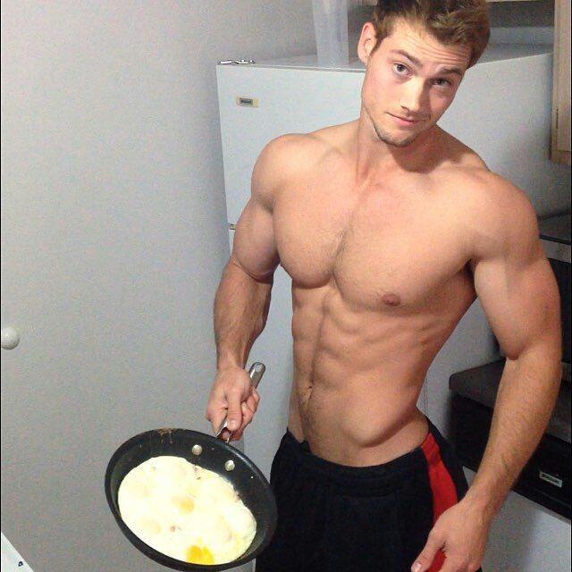 Chico guapo cocinado huevos