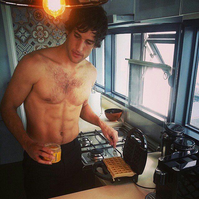 Chico guapo en la cocina preparando wafles