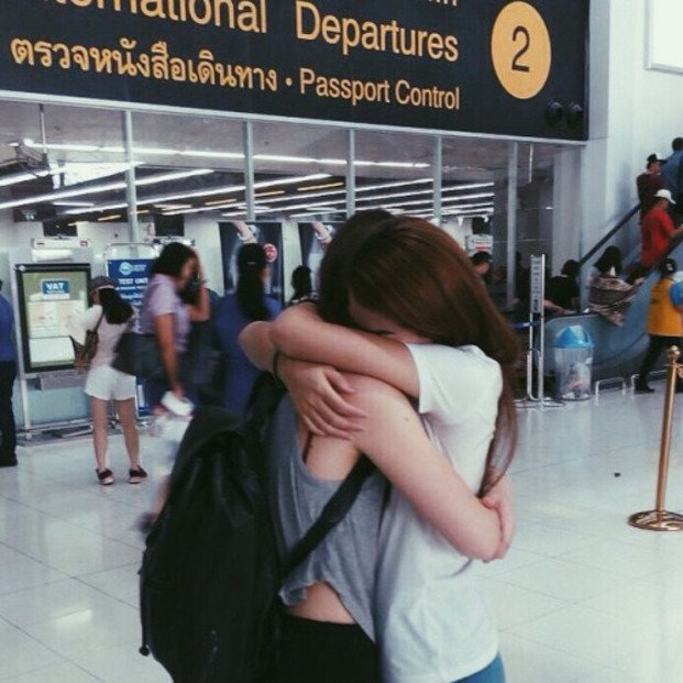 Chicas abrazándose en un aeropuerto