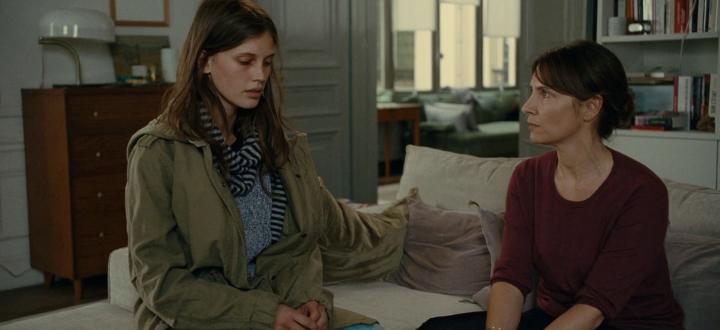Madre e hija sentadas en un sofá conversando