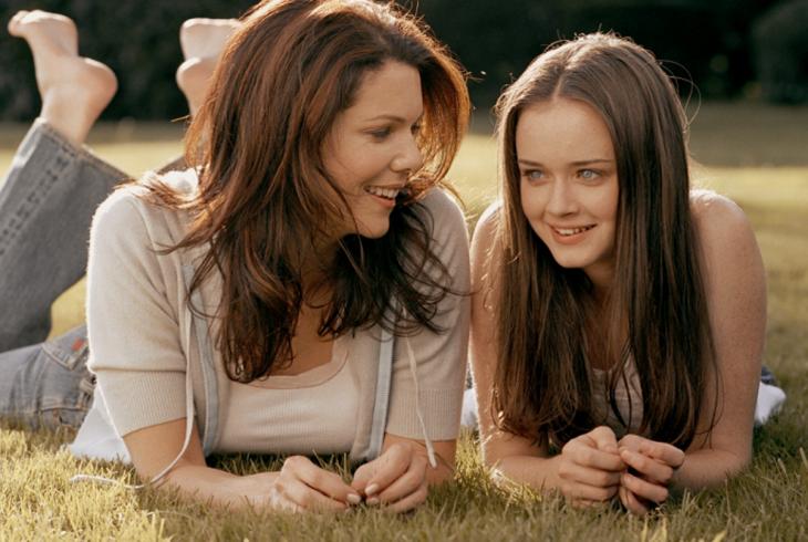 Escena de la serie gilmore girls. Madre e hija sentadas en el pasto
