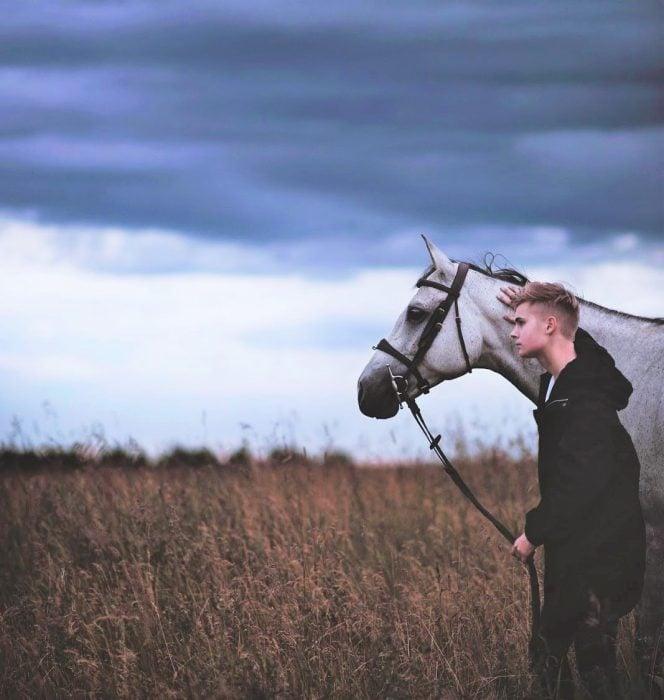 chico de pie caminando con un caballo blanco