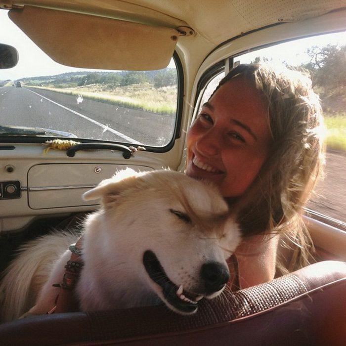 Chica y su perro de paseo en un carro