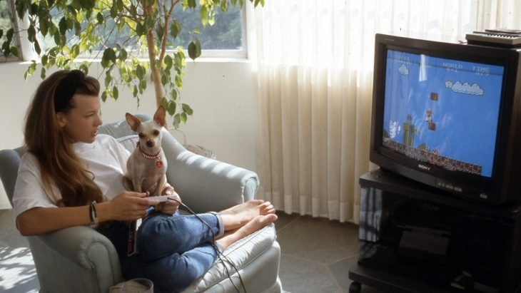 Chica jugando videojuegos junto a su perro chihuahua