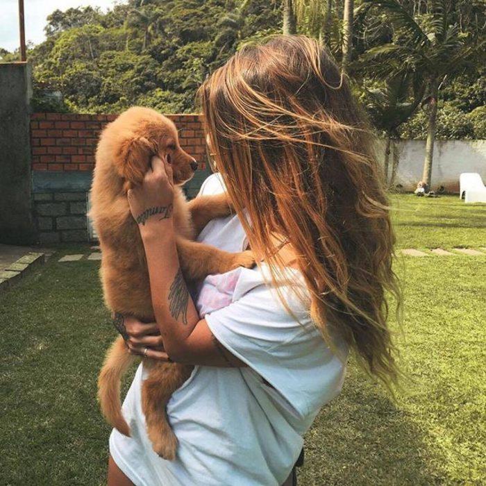 Chica cargando a un cachorro golden