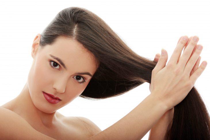 Chica aplicando aceite de oliva en su cabello