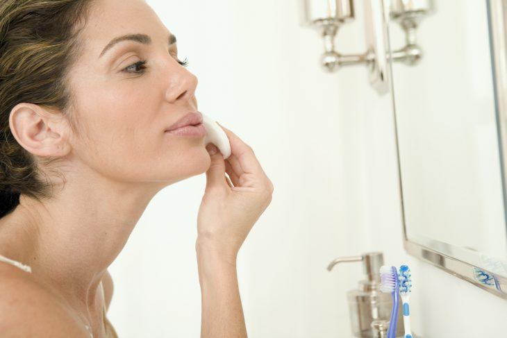 Chica desmaquillándose frente al espejo