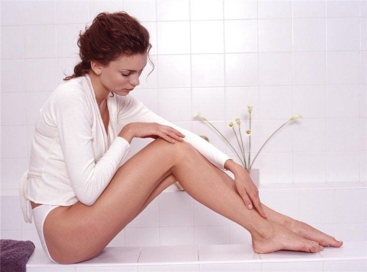 Chica tocando sus piernas después de depilarlas