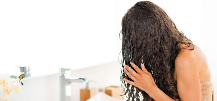 Chica aplicando tratamiento en el cabello después de bañarse