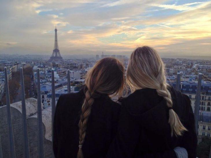 dos mujeres de espaldas con trenzas y torre eifel