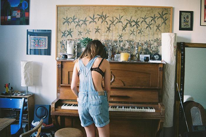 mujer con overol de espaldas tocando el piano