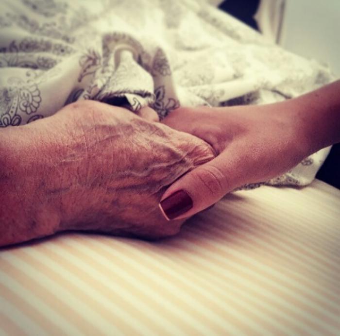 mano de abuelo y mano de mujer en la cama