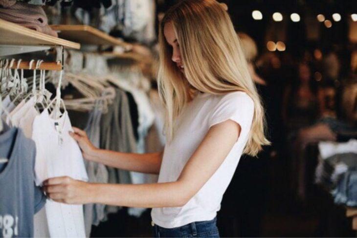 chica rubia elige ropa en una tienda