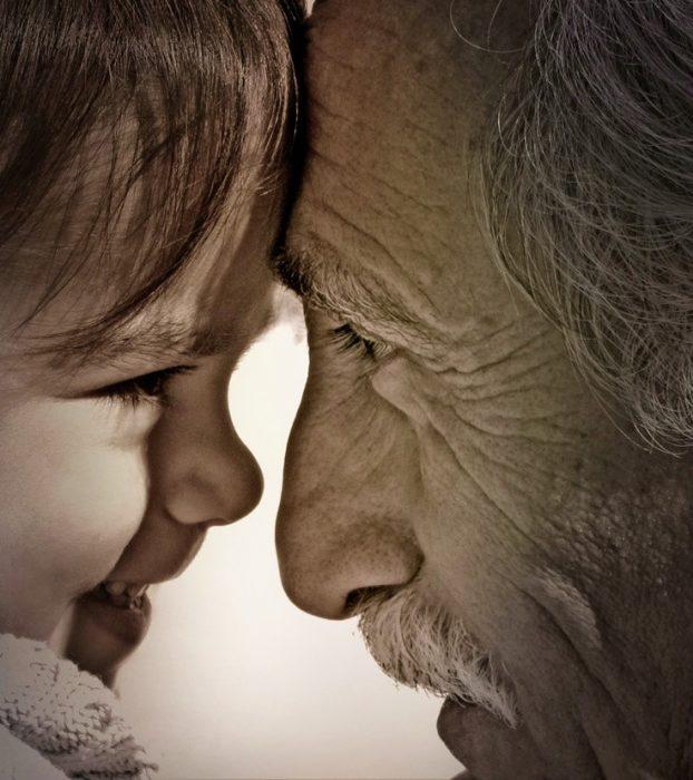 abuelo y nieta de frente sonrien