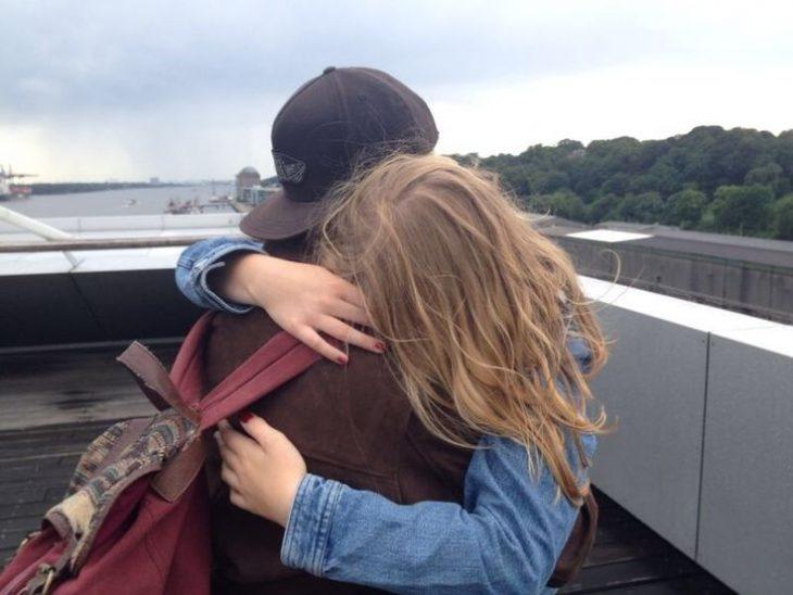 pareja abrazandose en un balcón rubia y chico con gorra