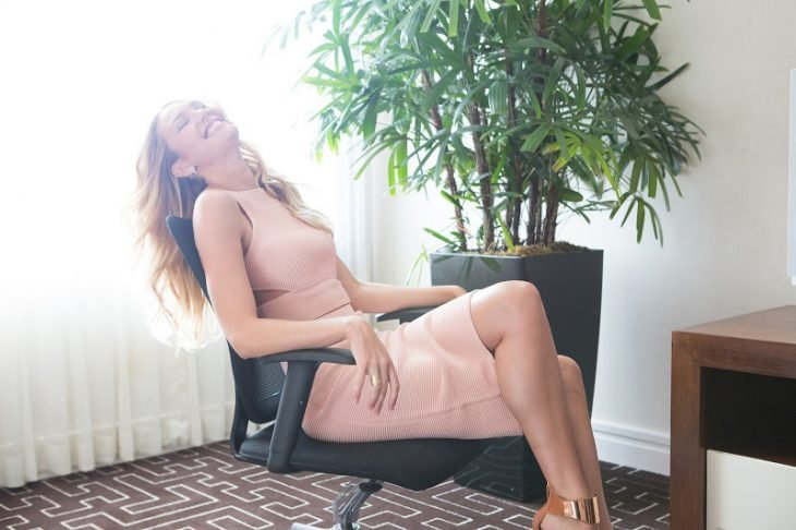mujer feliz ejecutiva vestido rosa silla de oficina