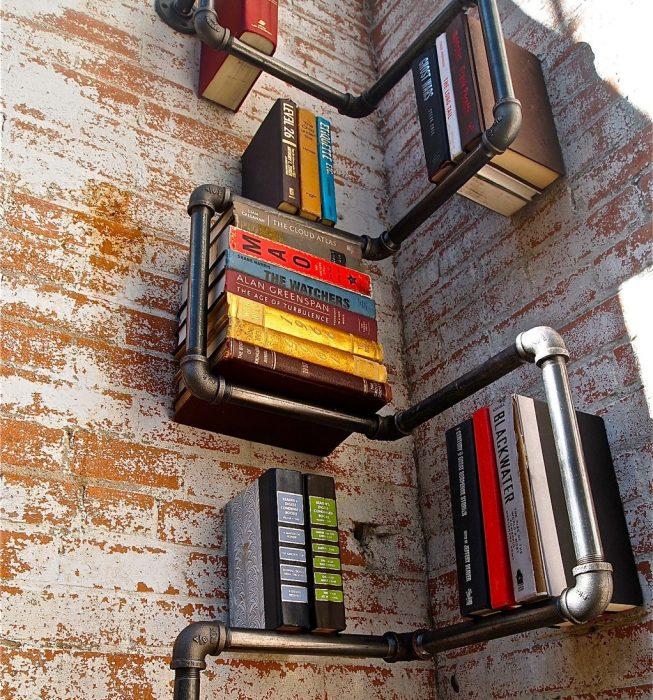 libros acomodados en tuberia de agua en un rincon