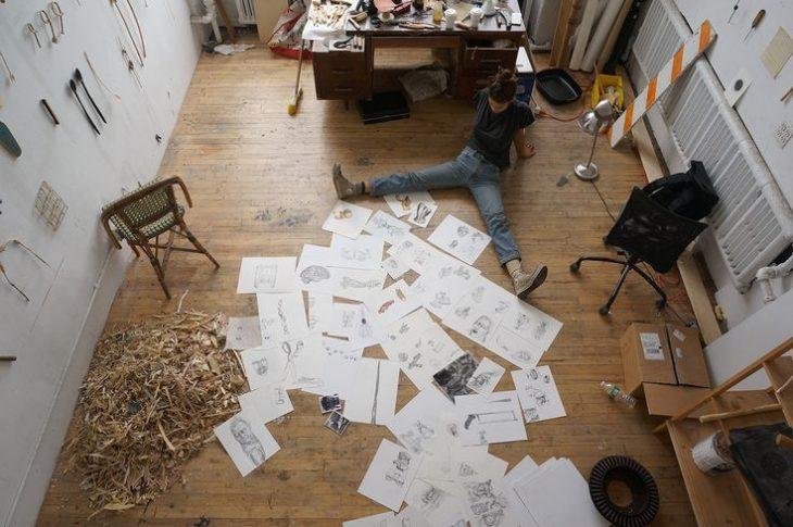 mujer sentada en el suelo de taller con dibujos