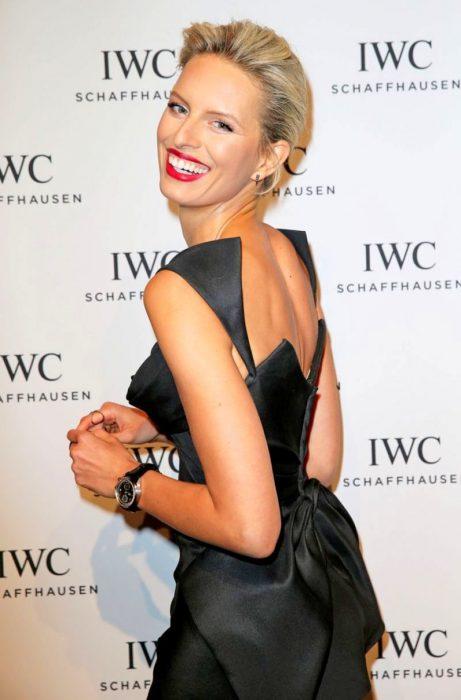 mujer rubia con vestido negro sonriendo