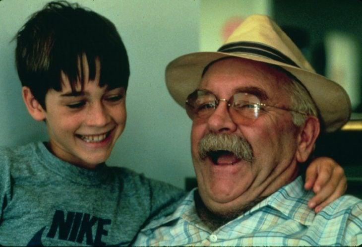 niño y abuelo con lentes y sombrero riendo