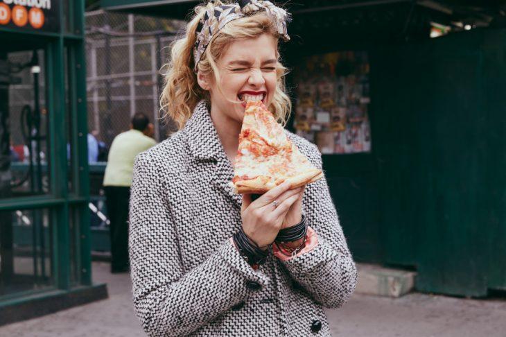 Chica mordiendo una rebanada de pizza
