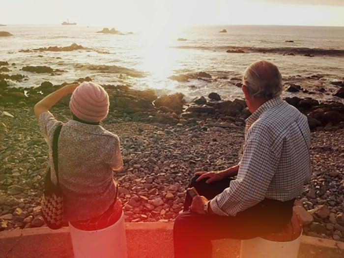 abuelo y nieta en la orilla del mar de espaldas