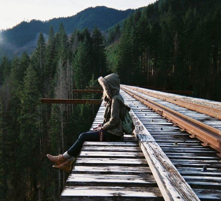chica con abrigo en un puente sobre las montañas
