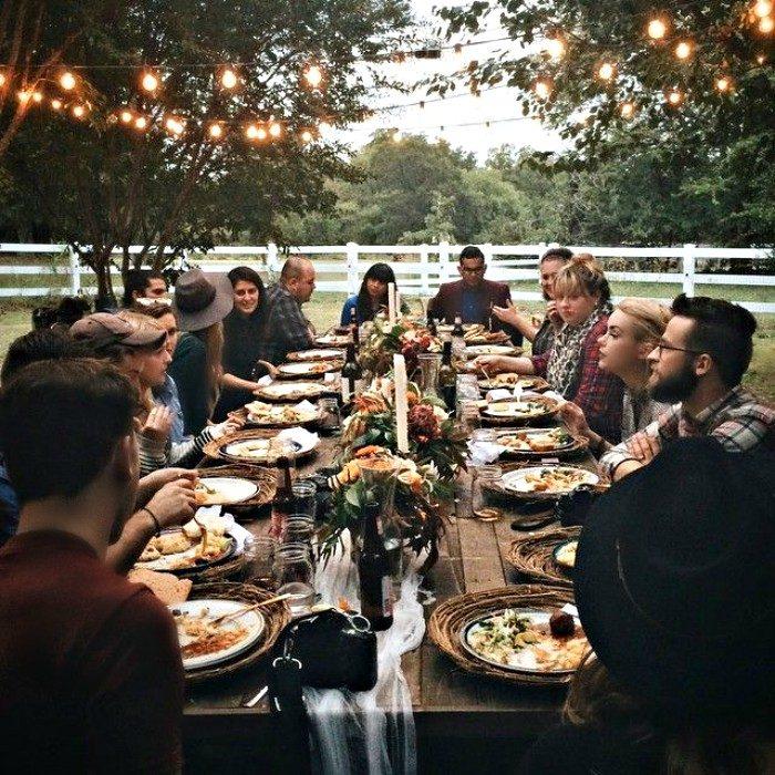 familia en comida familiar con larga mesa y luces