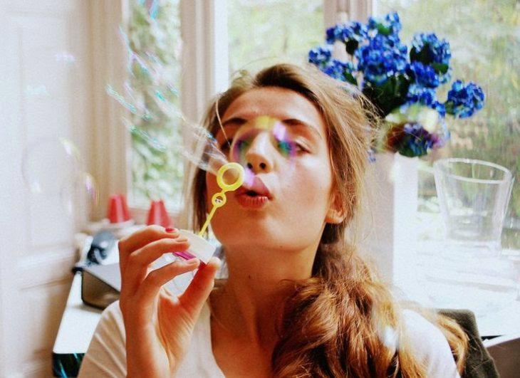chica jugando con burbujas y flores azules atrás