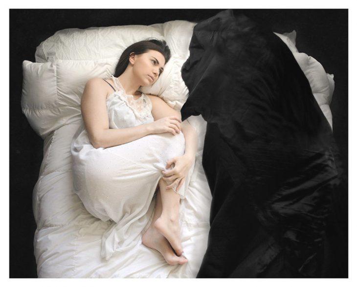 mujer acostada al lado de la cama con cobija negra